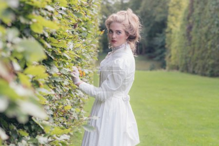 Photo for Retro victorian woman walking in garden touching tall hedge. - Royalty Free Image