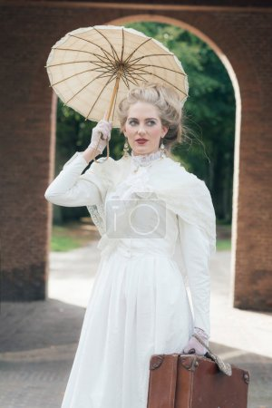 Victorian fashion girl with umbrella standing in f...