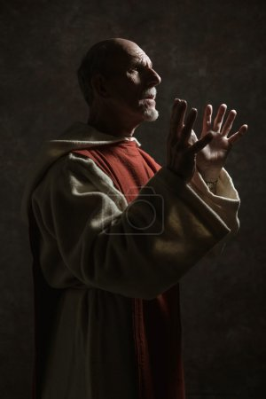 Photo for Side view portrait of wishing monastic. Studio shot against dark wall. - Royalty Free Image