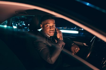 Man in car at night calling with smartphone. Looki...