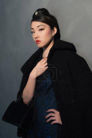 Photo pour Élégant riche asiatique femme dans les années quarante rétro mode avec sac à main. Debout contre le mur . - image libre de droit
