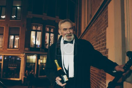 Smiling man in tuxedo with bottle