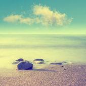 Minimalist misty seascape with rocks at long exposure. Coastal Sunrise.
