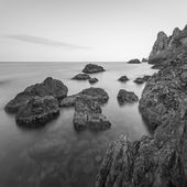 Minimalist misty seascape with rocks at long exposure. Black and white