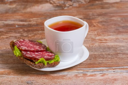 Breakfast with salami sandwich and cup of tea