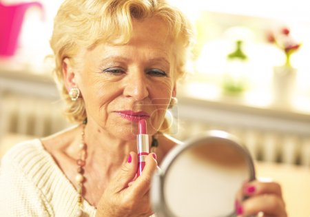 Elderly woman applied lipstick and looked in the mirror