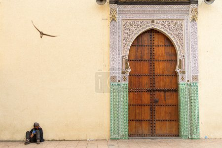 FEZ, MOROCCO - APRIL 15: Unkown man relaxing near to entrance of