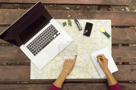 Planning travel on wood table outside with map, laptop, knife, n