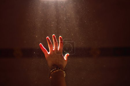 Woman hand into the light