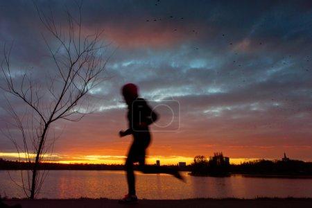 Man running at sunset on lake...