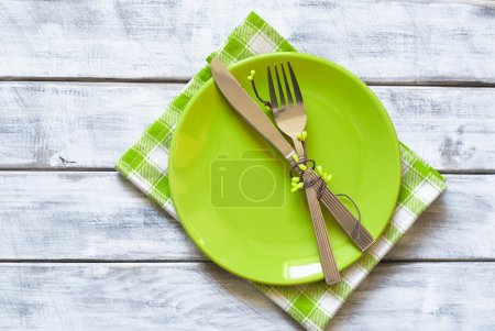Foto de Spring table setting with green plate over wooden table background. View from above with copy space - Imagen libre de derechos