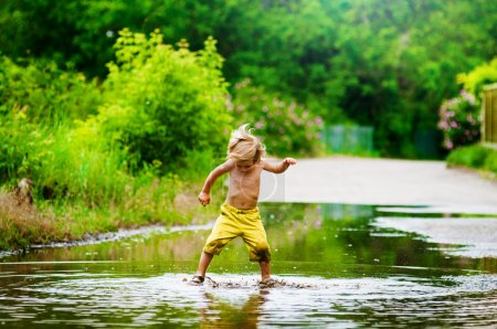 Little boy runs through a puddle. summer outdoor...