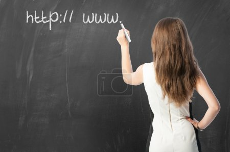 Woman writing URL on blackboard