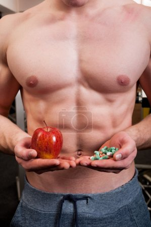 Muscle man choice between apple and pills