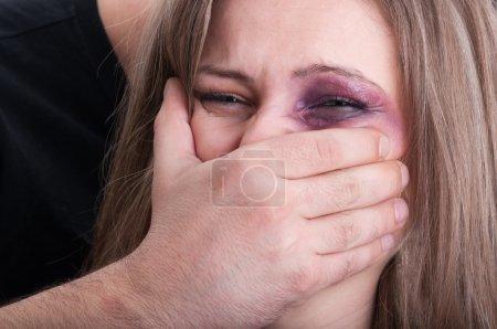 Aggressive man grabbing beaten woman mouth