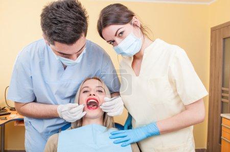 Dental team and beautiful female patient. Healthca...