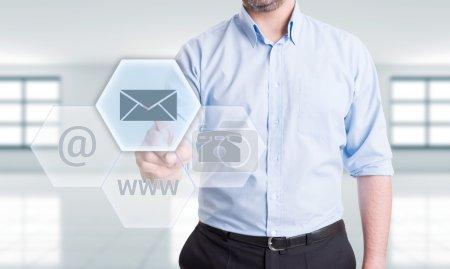 Photo pour Contactez-nous en utilisant le concept d'adresse e-mail avec l'homme appuyant sur le bouton sur écran tactile futuriste transparent - image libre de droit