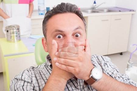 Photo pour Homme effrayé chez le dentiste couvrant sa bouche. Douleur dans le concept ou l'idée de cabinet dentaire - image libre de droit