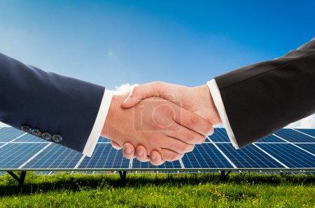 Foto de Apretón de manos de los empresarios sobre fondo de panel fotovoltaico solarpower como acuerdo de equipo de negocio de bioenergía - Imagen libre de derechos
