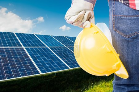 Foto de Ingeniero con casco de construcción amarillo sobre fondo de paneles de energía solar - Imagen libre de derechos