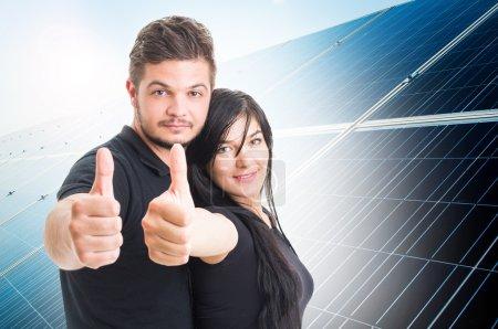 Foto de Pareja feliz mostrando como en el fondo del panel fotovoltaico de energía solar como concepto de solución de energía verde - Imagen libre de derechos