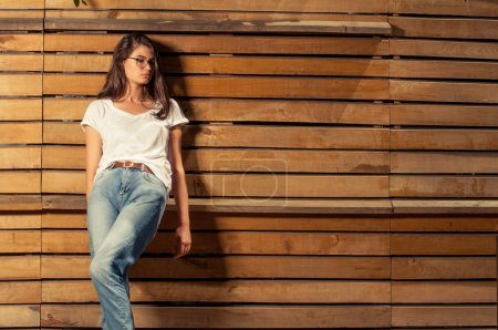 Photo pour Modèle féminin belle hipster sur fond de clôture en bois portant des lunettes de vue - image libre de droit
