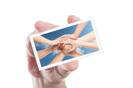Hand holding volunteer card with joined hands as background