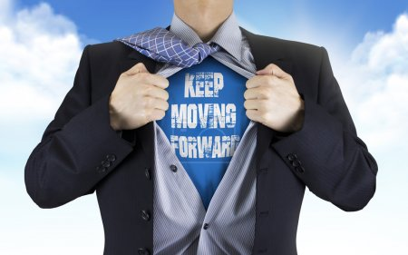 businessman showing Keep moving forward words underneath his shi