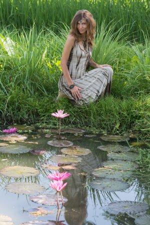 Photo pour Belle fille dans la nature près du lac avec des lis et une rizière à Bali, Indonésie - image libre de droit