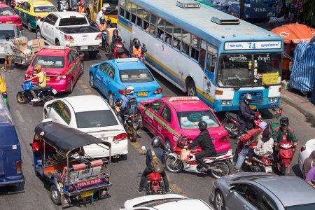 Traffic moves slowly along a busy road in Bangkok, Thailand.