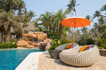 Swimming pool and beach chairs in a tropical garden, Thailand