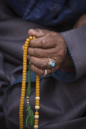 Old Tibetan woman holding buddhist rosary, Ladakh, India