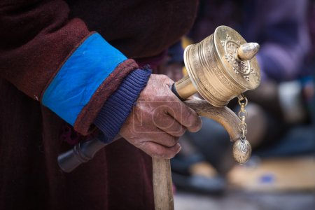 Old Tibetan man holding wooden walking stick and buddhist prayer wheel, Ladakh, India