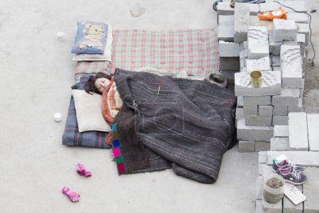 Indian girl sleeping on the street next to monastery of Lamayuru, Ladakh, India
