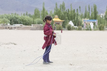 Tibetan girl jumping on a skipping rope in Druk White Lotus School. Ladakh, India