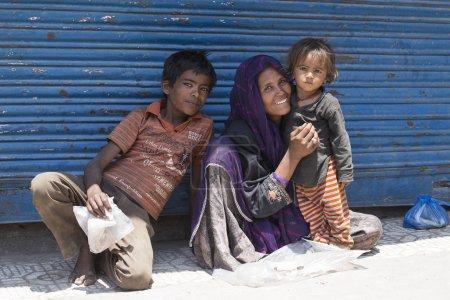 Indian poor woman with children begs for money from a passerby on the street in Srinagar, India