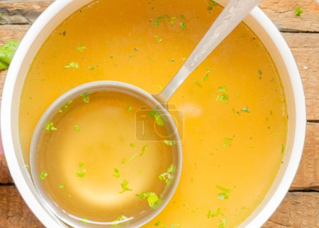 Saucepan with broth on the table
