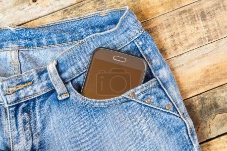 Smart phone in pocket blue jeans
