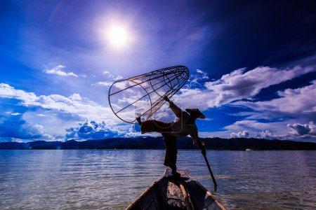 Fischer auf Boot fangen Fisch mit traditionellem Netz