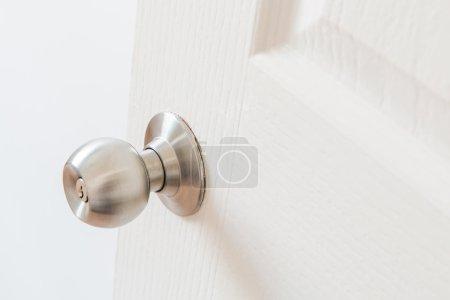 Detail of a metallic knob on white door