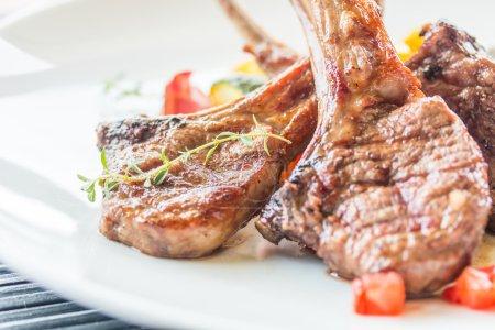 Photo pour Steak d'agneau, côtelettes d'agneau servies sur assiette blanche au restaurant - image libre de droit