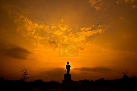 Buddha statue silhouette over sunset