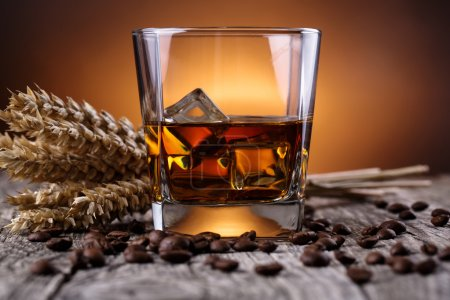 Glass of whiskey with ice and wheat on a wooden table.