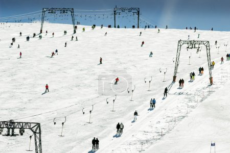 Skiing people, the chair lifts and rope tow systems of Zell am See ski region in Austria