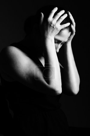 Woman prays on a black background