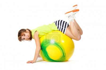 Girl with yellow ball doing exercises on a white b...
