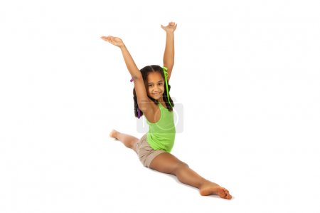 girl is engaged in gymnastics. child sitting on the splits. isolated on a white background