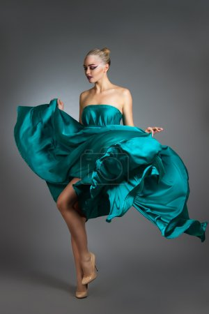 Photo pour Femme en robe de soie ondulant sur l'énergie éolienne. Volant et flottant chiffon robe plus gris fond femme danse en robe de mode - image libre de droit
