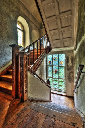 Stairway with stained glass windows in an abandoned manor