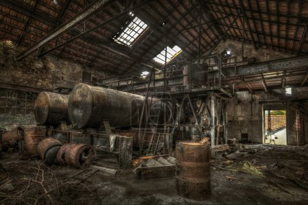 Rusty cisterns and barrels in an abandoned factory